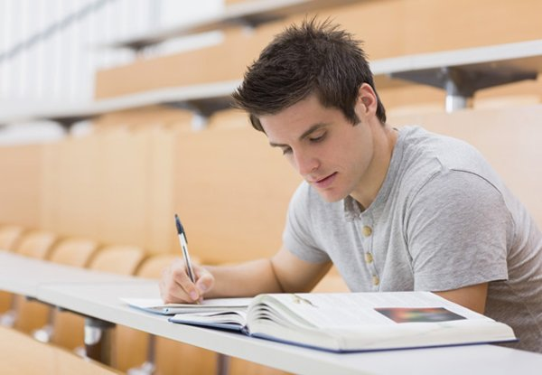 Student sitting reading a book and taking notes